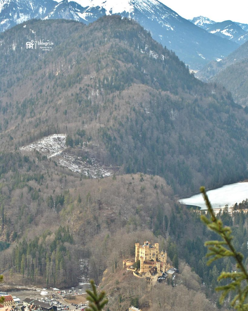 View of the Hohenschwangau Castle from Neuschwanstein with the backdrop of snowy Alps
